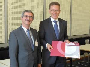 Dr. Ümit Ertürk (Mitglied des DGQ-Vorstands, links) gratuliert Dr. Michael Garmer zur 20-jährigen DGQ-Mitgliedschaft.